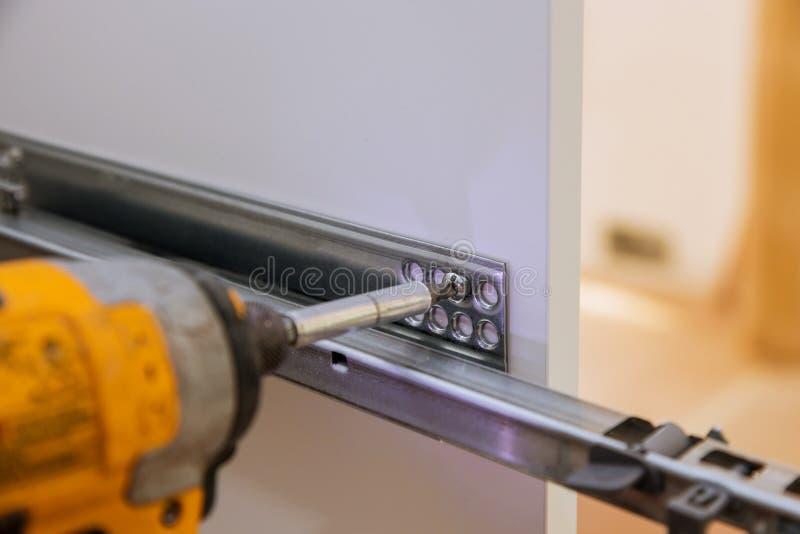Złotej rączki usługa w trakcie gromadzić i wspinać się meblarskie kuchenne szafy i gabineta śrubokręt obraz stock