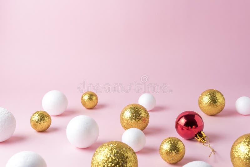 Złoto i biel połyskujemy balową dekorację z czerwonym Bożenarodzeniowym bauble na różowym tle obrazy royalty free