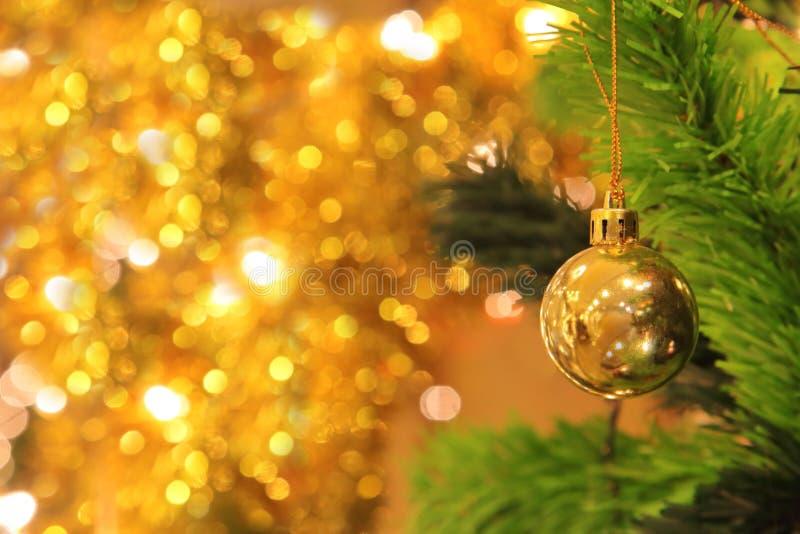 Złoty balowy obwieszenie na choinki gałąź z złocistym bokeh tłem dla świętowanie projekta z kopii przestrzenią i karty fotografia stock