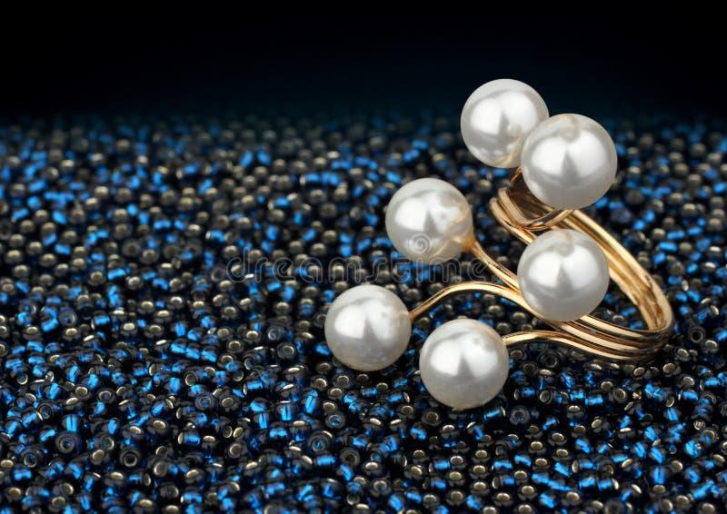 Złoty biżuteria pierścionek z perłami na zmroku - błękitni koraliki zdjęcie royalty free