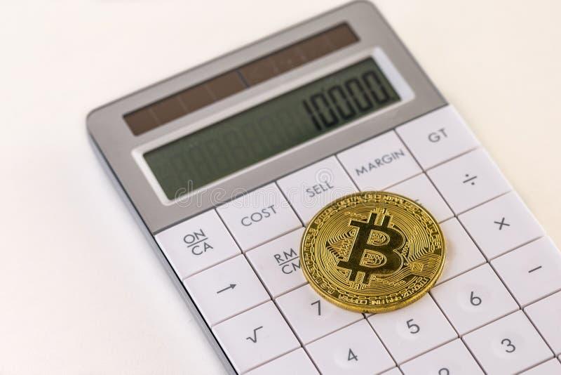 Złoty bitcoin na białym kalkulatora i śmietanki stole obrazy royalty free