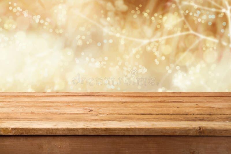 Złoty bokeh tło z pustym drewnianym stołem dla produktu montażu pokazu fotografia stock