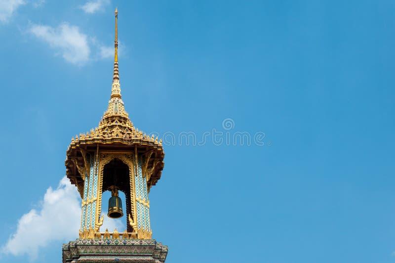 Złoty Dzwonkowy wierza z Złotym świątyni i niebieskiego nieba tłem przy Watem Phra Kaew, Królewski Uroczysty pałac, Bangkok, Tajl obraz royalty free