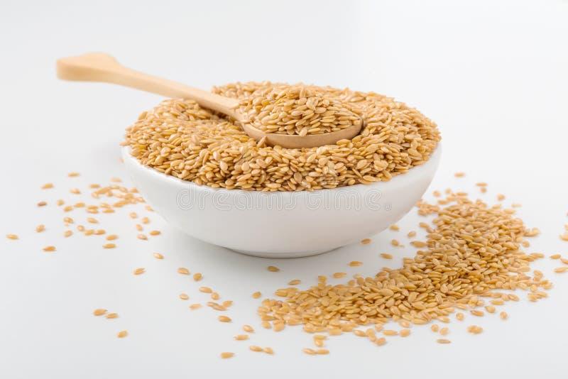 Złoty flaxseed w drewnianej łyżce i pucharze fotografia stock