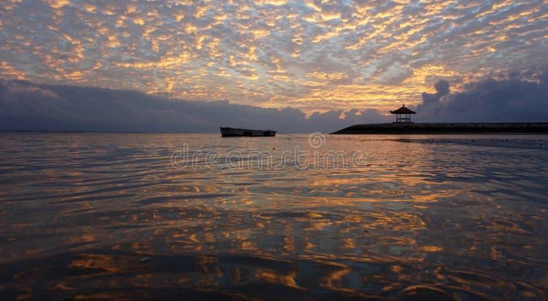 Złoty i kolorowy wschód słońca niebo Złoci wschód słońca chmur koloru odbicia na wodzie Ranek sceneria Sanur plaży natury plaża zdjęcie stock