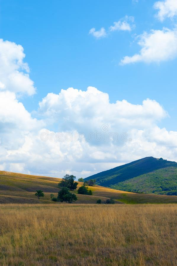 Złoty jak łąki, zieleni wzgórza i biel chmury na błękitnym tła niebie, zdjęcia royalty free