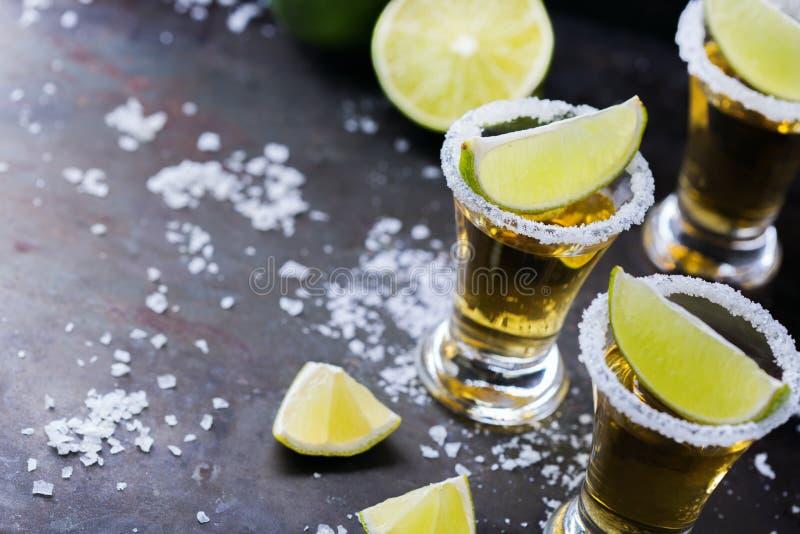 Złoty meksykański tequila strzał z zielonym wapnem i solą obraz stock