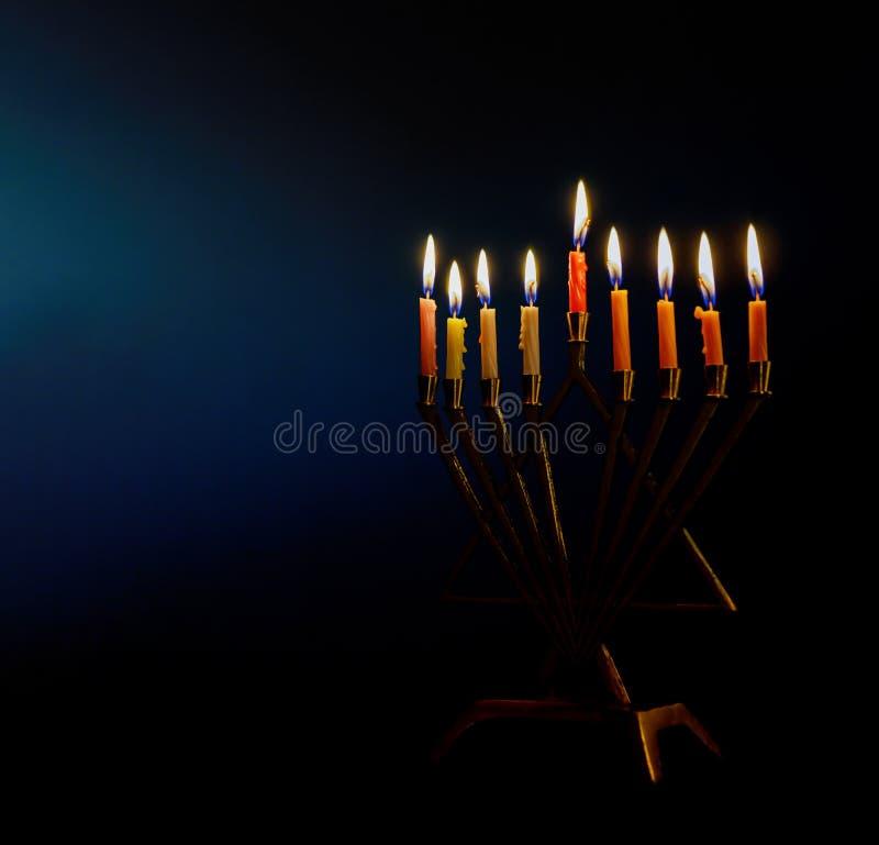 Złoty menorah zaświecał świeczki na menorah dla żydowskiego wakacyjnego Hanukkah obrazy royalty free