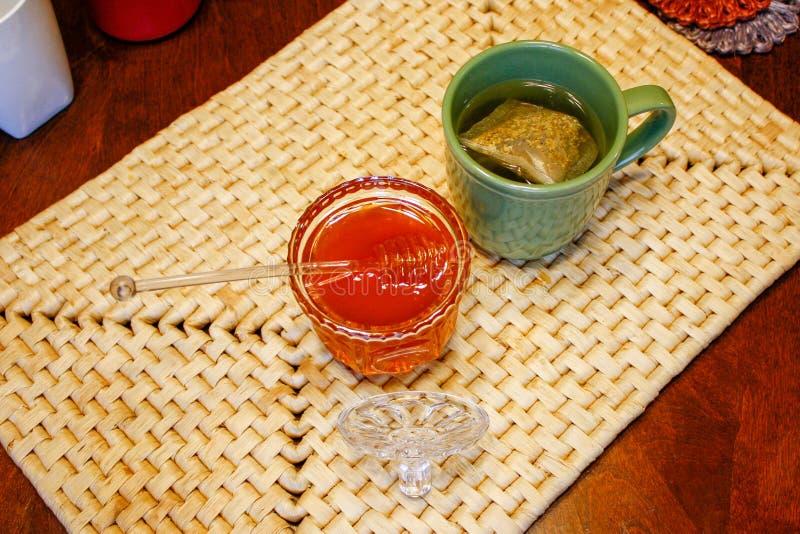 Złoty miód w szklanym słoju obok moczyć herbaty na tkanej miejsce macie fotografia royalty free