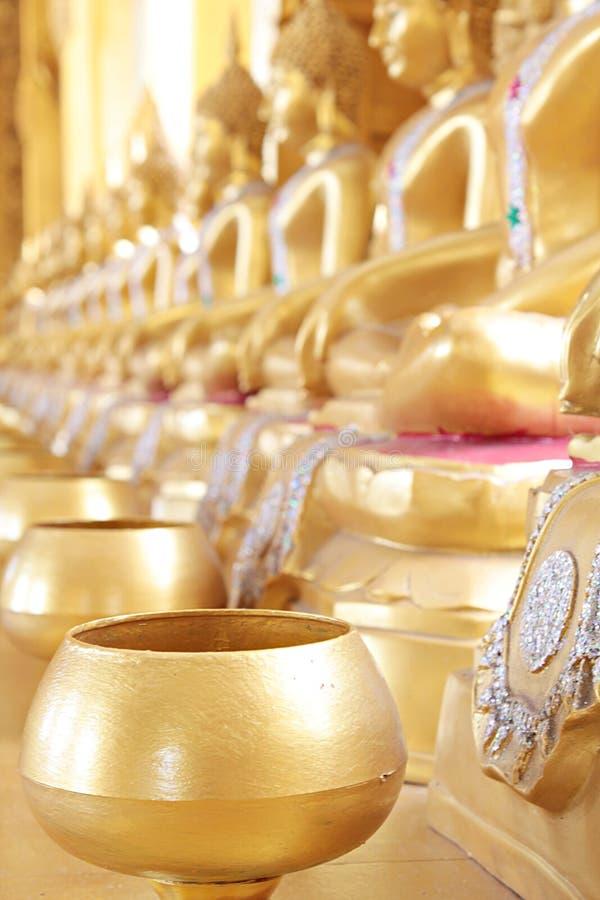 Złoty monk& x27; s datków puchar i złota Buddha statua obrazy royalty free