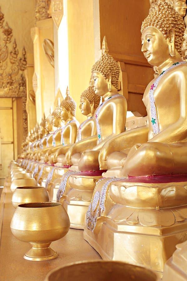 Złoty monk& x27; s datków puchar i złota Buddha statua zdjęcie royalty free