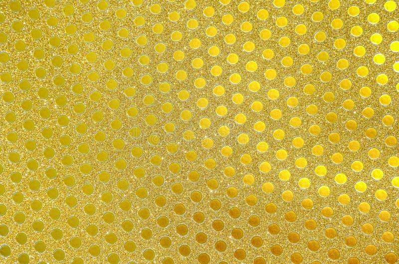 Złoty opakunkowy papier, migotanie mali okręgi deseniuje jako tło lub tekstura obrazy royalty free