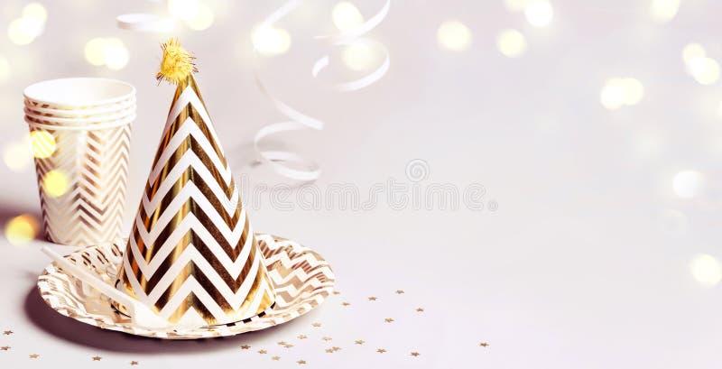 Złoty pasiasty szyszkowy kapelusz i inny bawimy się akcesoria Bokeh confetti i światła Sztandaru format zdjęcie stock