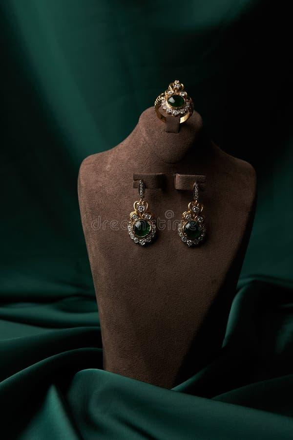 Złoty pierścionek i para kolczyki z zielonym szmaragdem i diamentami obraz royalty free