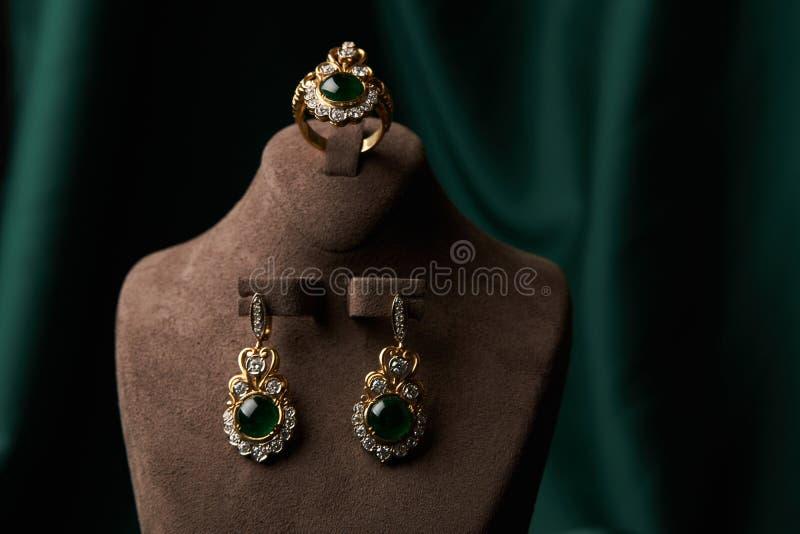 Złoty pierścionek i para kolczyki z zielonym szmaragdem i diamentami zdjęcia stock