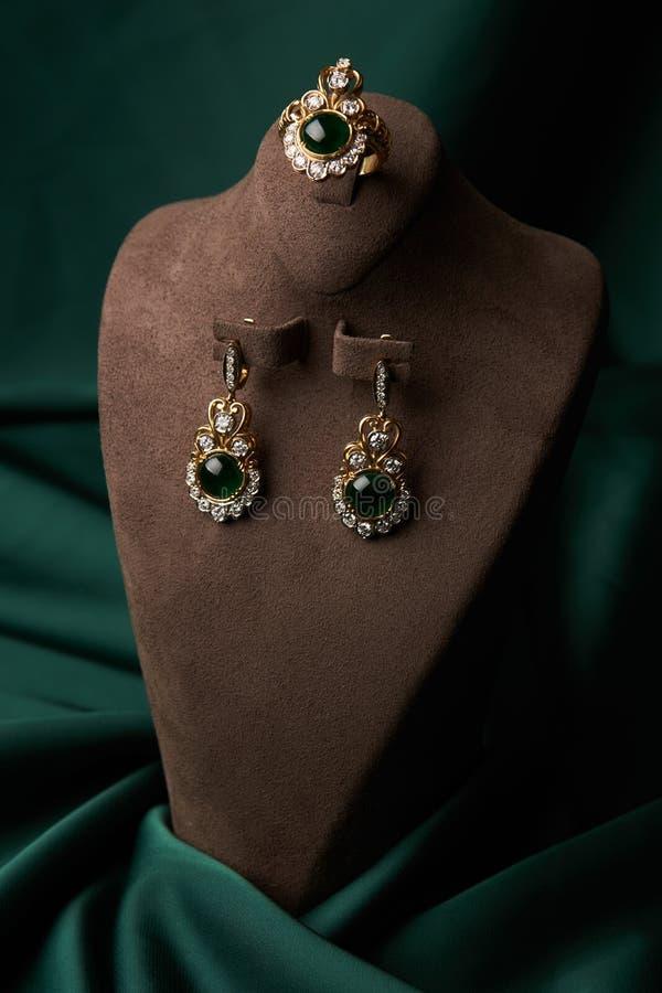 Złoty pierścionek i para kolczyki z zielonym szmaragdem i diamentami zdjęcie stock