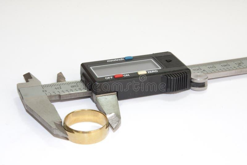 Złoty pierścionek w cyfrowym calliper zdjęcia royalty free