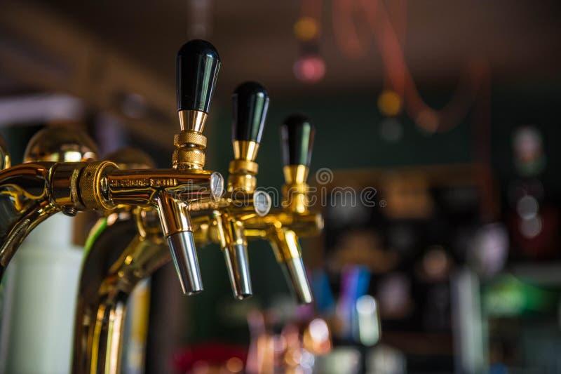 Złoty piwa klepnięcie z zamazanym tłem zdjęcia stock