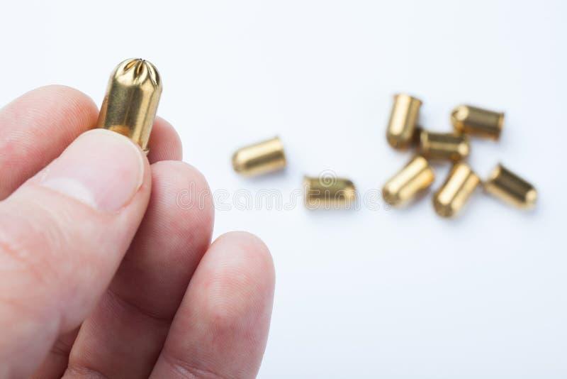 Złoty pocisk w ręce odizolowywającej na białym tle obrazy stock