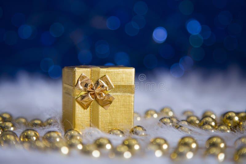 Złoty prezenta pudełko, koraliki z girlandą i zaświecamy na błękitnym bokeh plecy obrazy stock
