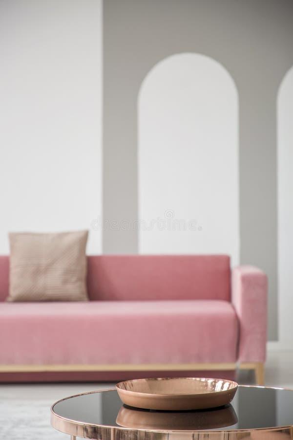Złoty róża puchar na błyszczącym czarnym stolik do kawy w eleganckim żywym izbowym wnętrzu z różową kanapą obraz stock