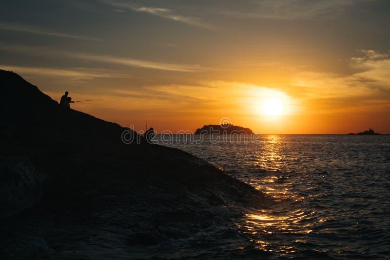 Złoty ranku światło na tropikalnej wyspie podczas gdy rybacy przygotowywają na skalistej falezie obraz royalty free
