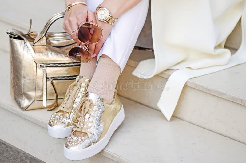 Złoty sneakers, torby i zegarka zbliżenie, Okulary przeciwsłoneczni zbliżenie w żeńskich rękach Dziewczyna siedzi na krokach ilustracja wektor