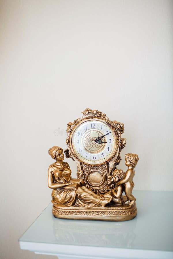Złoty stołowy zegar dekoruje z postaciami kobieta dwa chłopiec zdjęcia royalty free