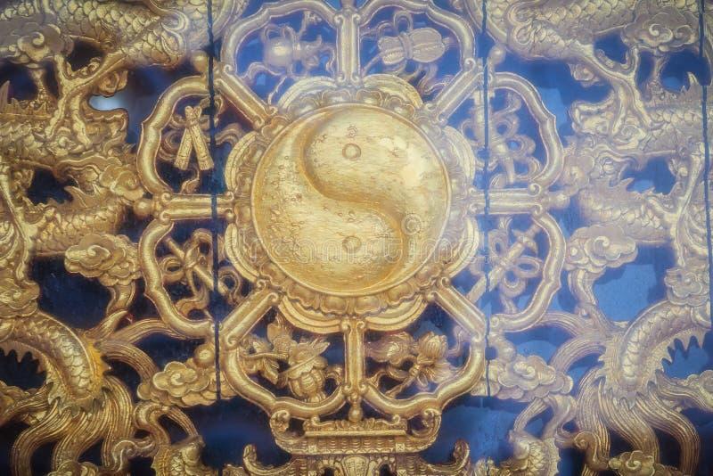 Złoty symbol Yin, Yang na ścianie Chińska świątynia w Tha - obraz royalty free
