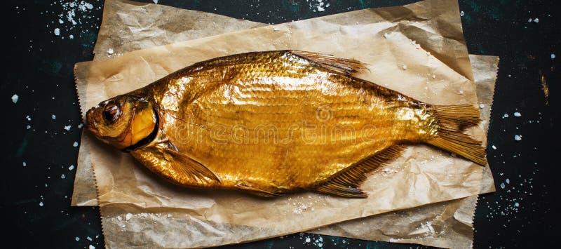 Złoty uwędzony rzeczny leszcz na ciemnym tle, odgórny widok zdjęcie royalty free