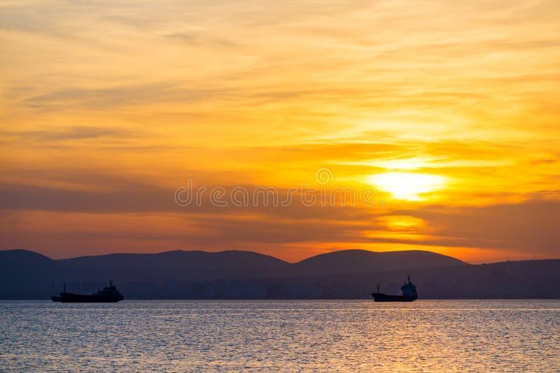 Złoty zmierzch, sylwetka miasto i ładunku statek, Piękny architecort morzem na tle zmierzch obraz stock