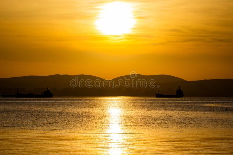 Złoty zmierzch, sylwetka miasto i ładunku statek, Piękny architecort morzem na tle zmierzch fotografia royalty free