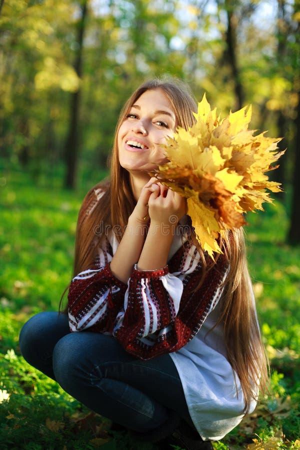 Z żółtymi liść roześmiana dziewczyna zdjęcie stock