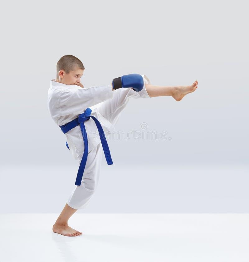 Z błękitnymi narzutami na rękach atleta trenuje kopnięcie nogę obrazy royalty free