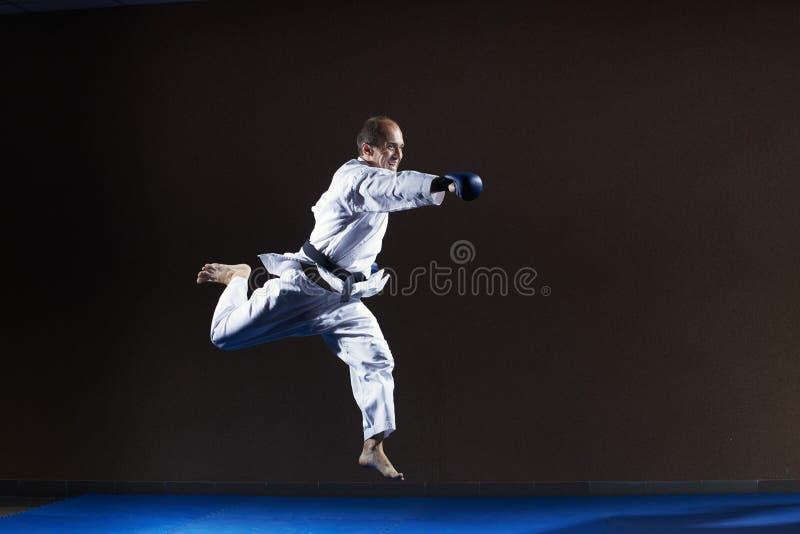 Z błękitnymi narzutami na rękach, atleta trenuje poncz rękę w skoku zdjęcie royalty free