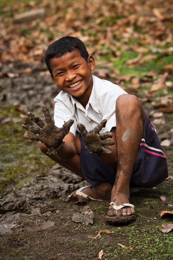 Z błotnistymi rękami uśmiechnięta Kambodżańska chłopiec s zdjęcia royalty free