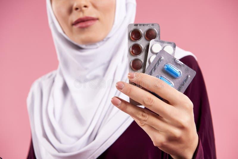 z bliska Arabska kobieta w hijab mienia pigułkach obrazy royalty free