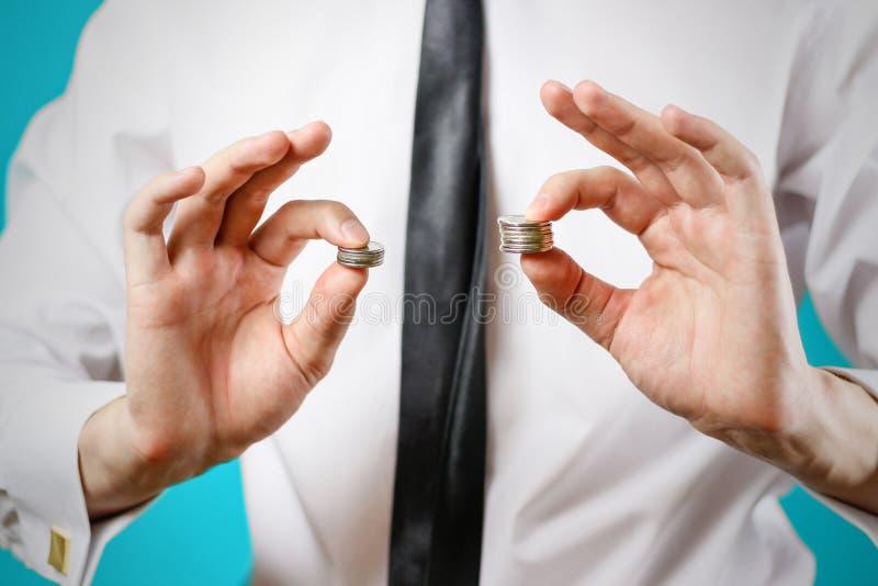 z bliska Biznesmen ręki porównują dwa stosu monety odróżniają się obrazy royalty free
