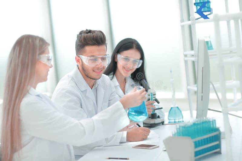 z bliska dru?yna naukowowie siedzi przy laboratorium sto?em zdjęcie stock