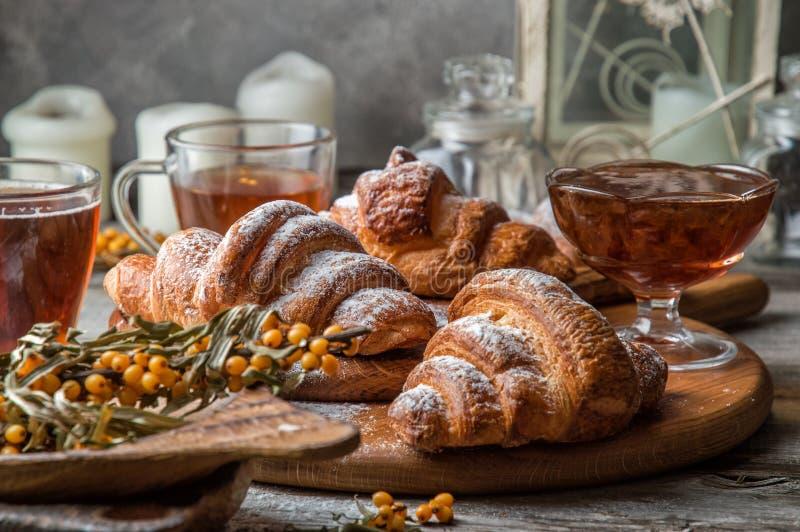 z bliska Francuscy croissants z złotym chipsem, kropiącym z sproszkowanym cukierem na wierzchołku Obok one jest różyczka dżem zdjęcie royalty free