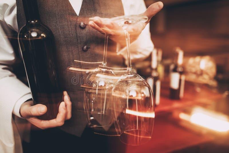 z bliska Sommelier w łęku krawacie trzyma z butelką wino i wina szkło zamazany zdjęcia stock
