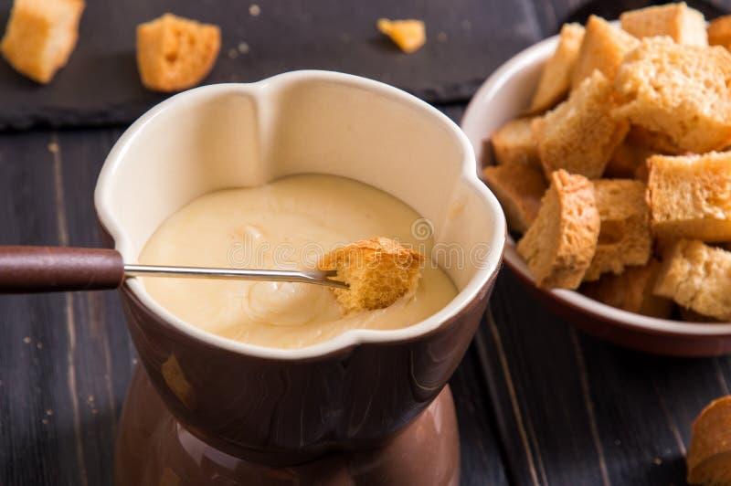 z bliska Tradycyjny francuski serowy fondue Crouton zamaczający w gorącego fondue z gruyere na wywodzącym się rozwidleniu fotografia royalty free