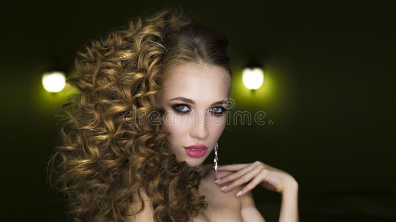 Z długimi kędzierzawymi włosami piękna młoda kobieta zdjęcie stock