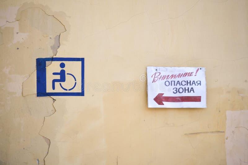 Z grubsza rysujący znak niepełnosprawna osoba na żółtej ścianie Talerz z inskrypcją w rosjaninie zdjęcia stock