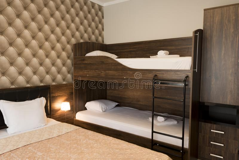 Z klasą hotelowej sypialni wewnętrzny projekt Wielki łóżko, łóżka Rodzinny pokój z brązu koloru brzmienia meble fotografia stock