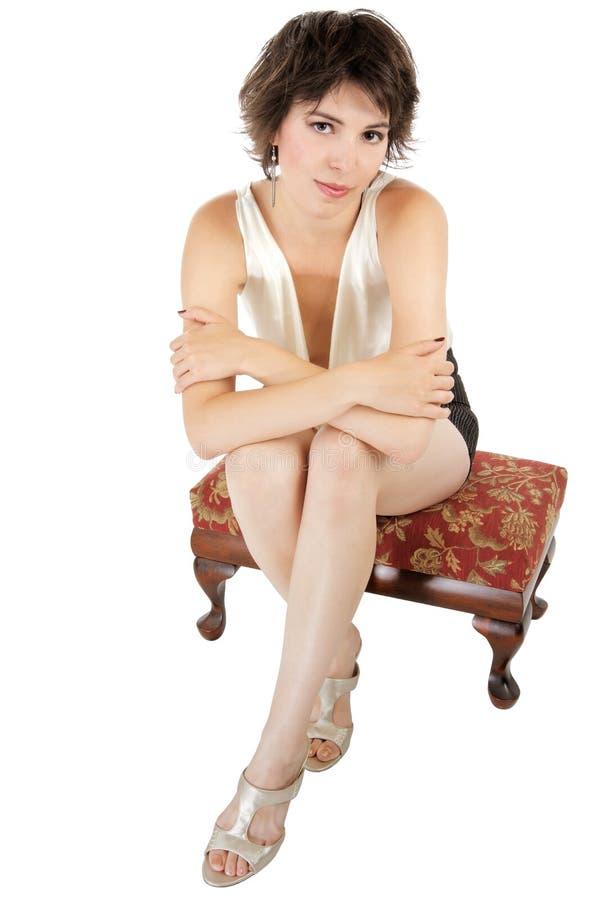 Z klasą modna młoda kobieta siedzi na ławeczce. fotografia stock
