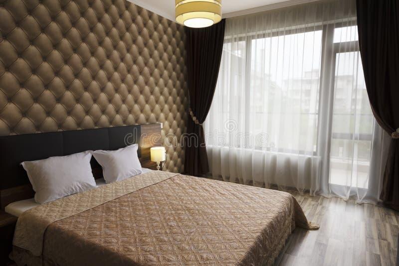 Z klasą sypialni wewnętrzny projekt Wielki łóżko, pokój z brown koloru brzmieniem Windows z długimi zasłonami, draperią i sheers, zdjęcia stock