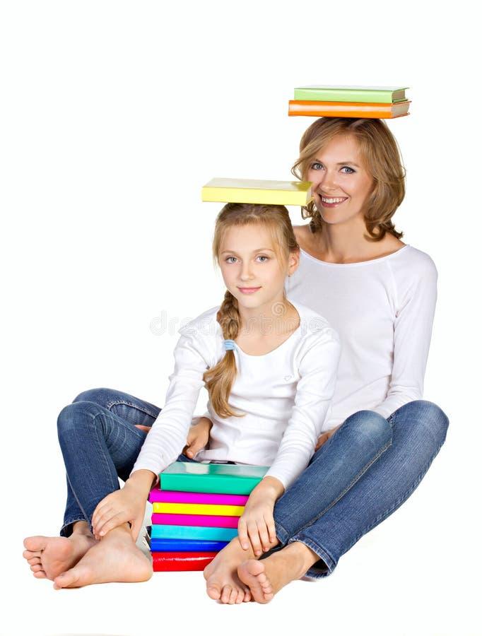 Z książkami matki i córki obsiadanie zdjęcia stock