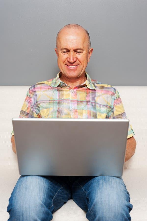 Z laptopem mężczyzna starszy obsiadanie w domu obraz stock