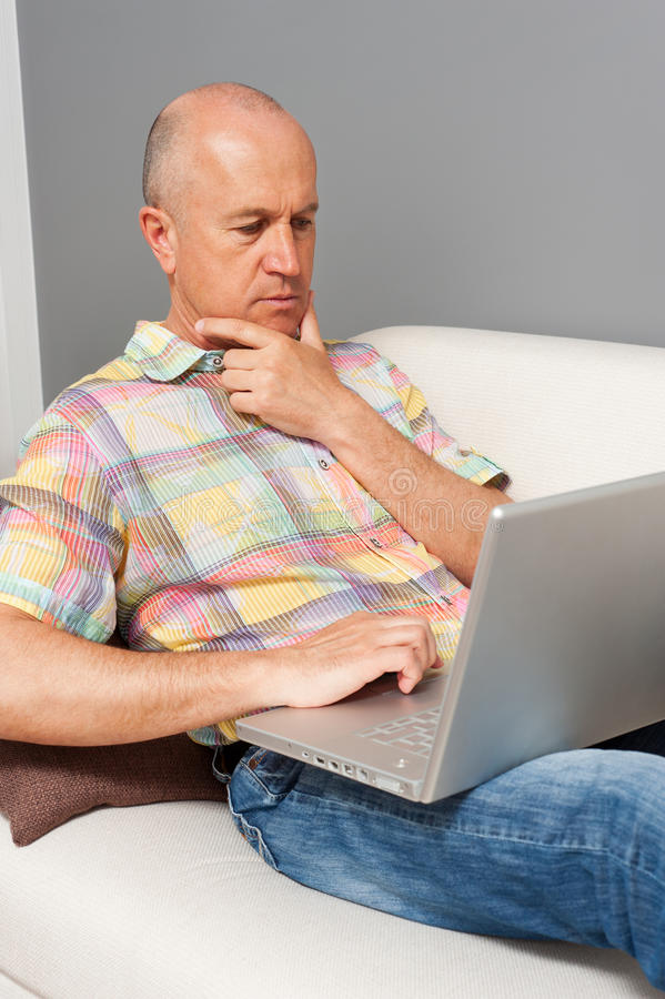 Z laptopem starszy mężczyzna w domu zdjęcia royalty free